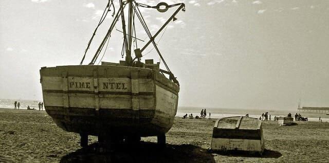 Stillliegendes Segelboot auf einem Strand mit badenden Touristen